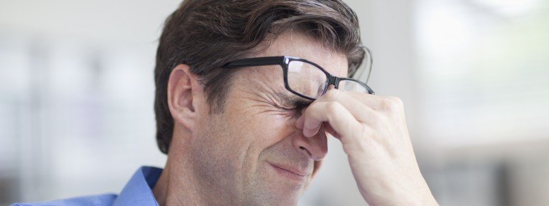 Mature man wincing with a headache
