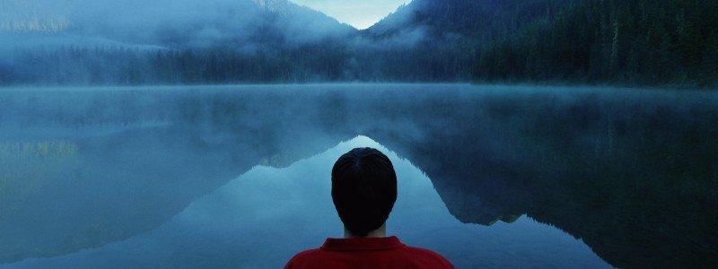 man seeking depression treatment looks across a misty lake