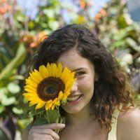 Woman Hiding Behind Sunflower To Overcome Shyness