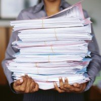 Man Carrying Stack Of Papers In An Office
