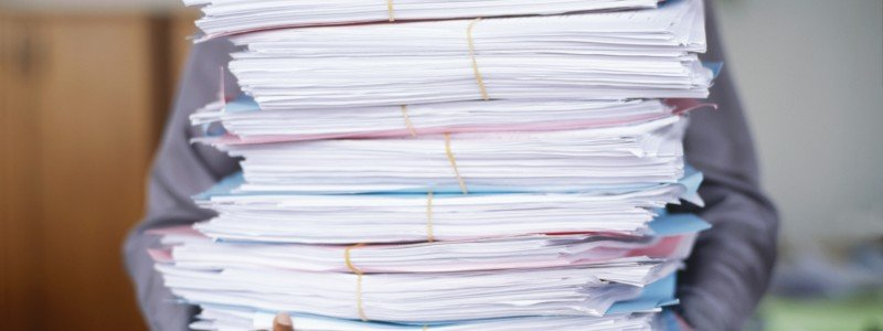 man with stacks of paper needs stress management help