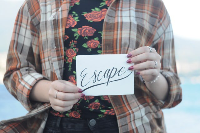 Person holding a sign saying escape symbolising they have escaped an unhealthy relationship